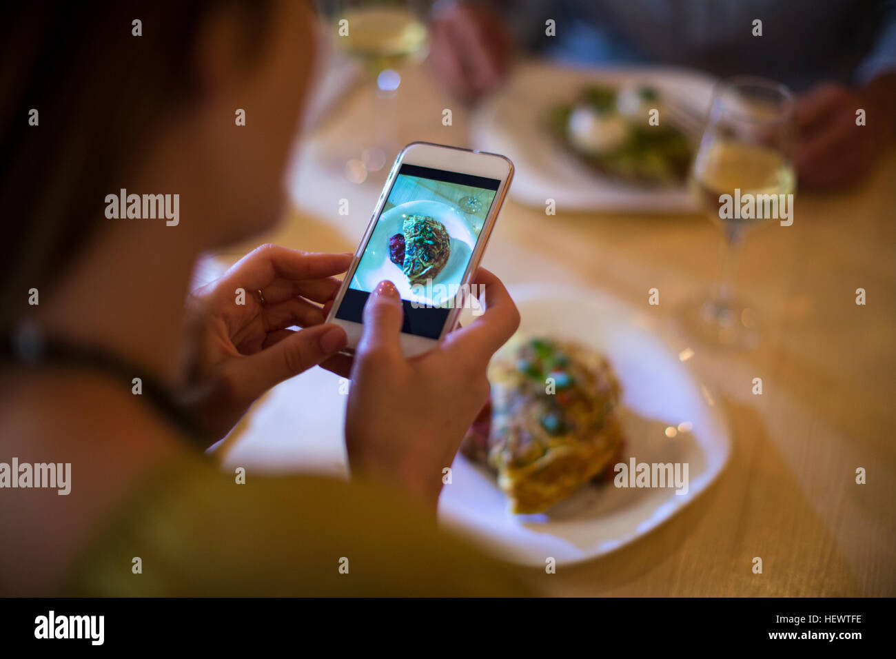 Woman taking photograph of her food on table - Stock Image