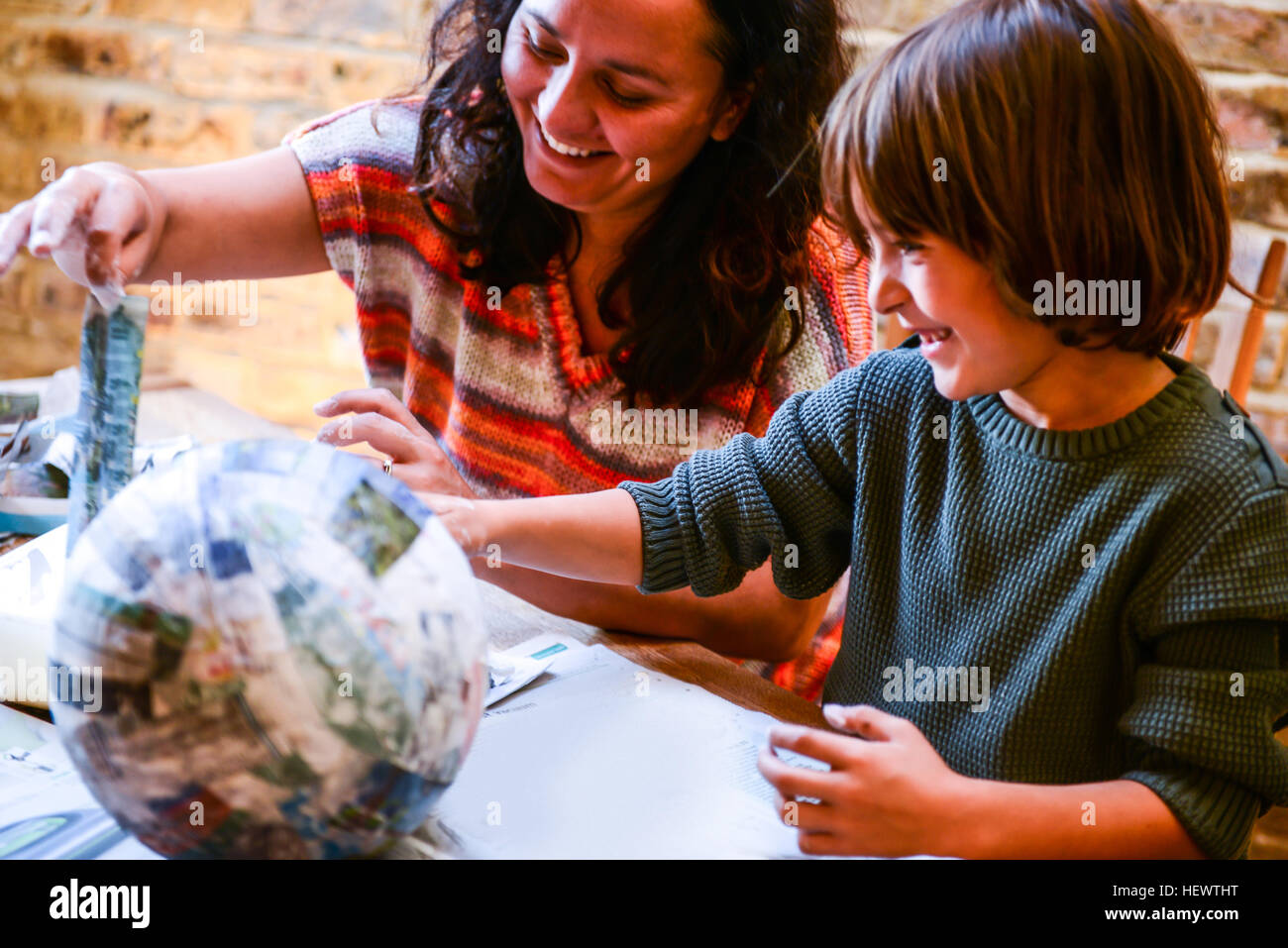 Child and mother playing with papier mache - Stock Image