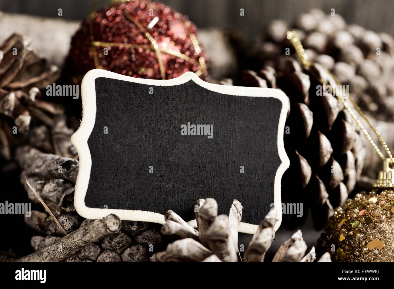 closeup of a black signboard with a blank space and some christmas balls on a pile of pine cones - Stock Image