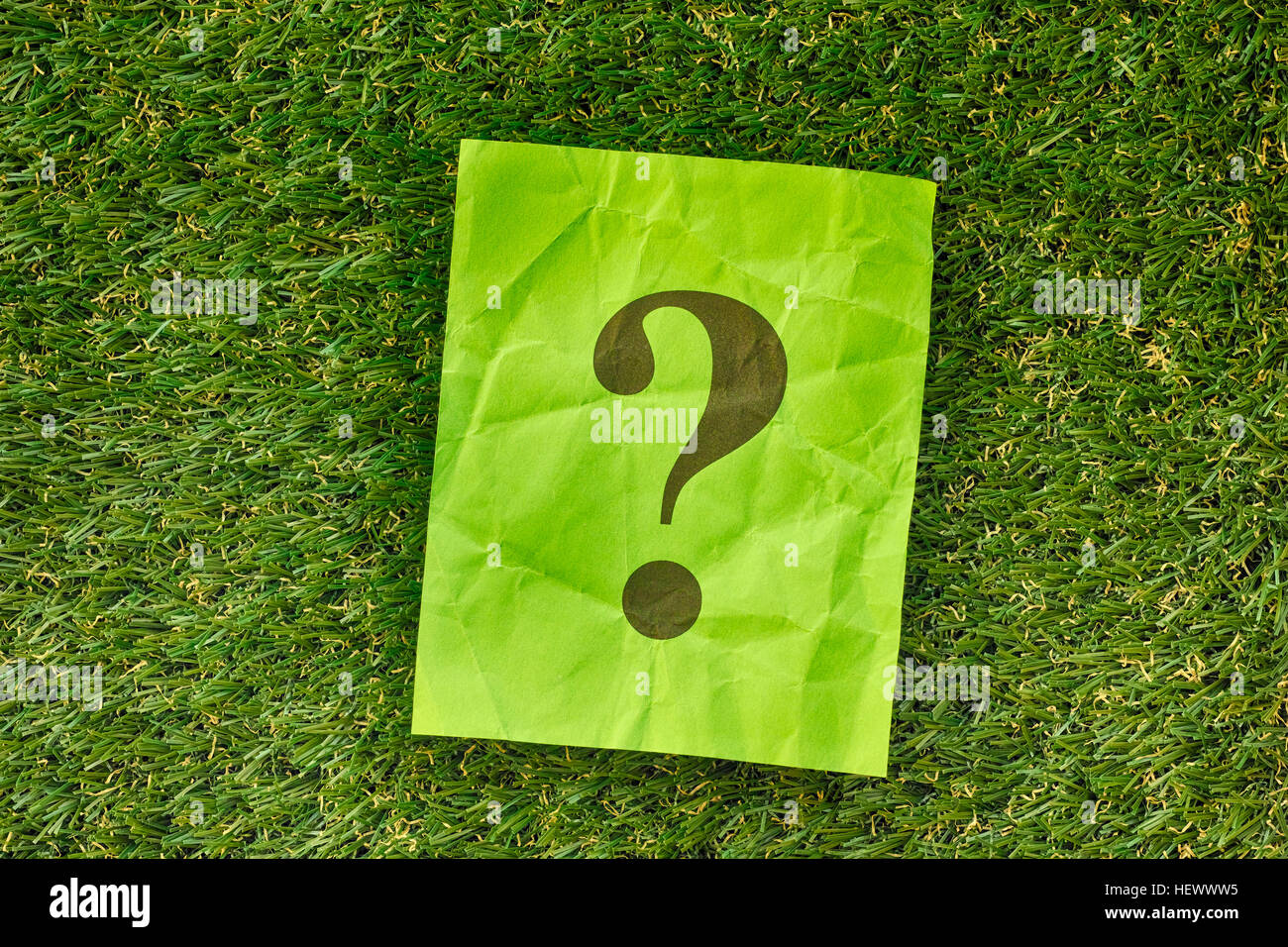 Green paper note with question mark on green grass. Close up. - Stock Image
