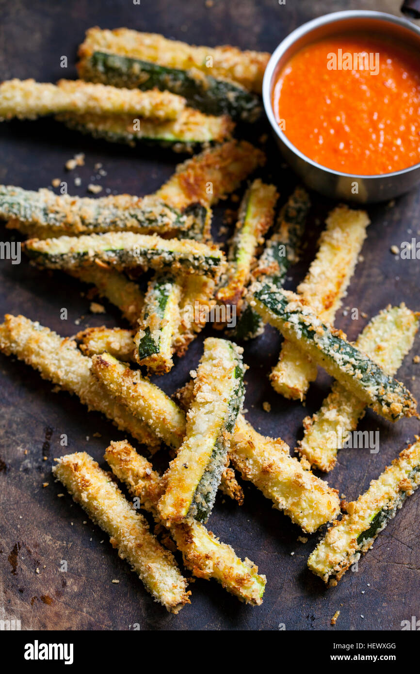 Zucchini fires with roast pepper and tomato sauce - Stock Image