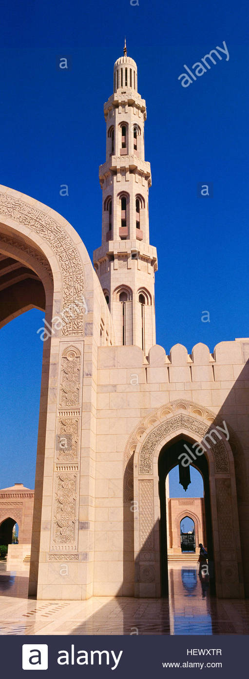 An ornate stone minarette towers over a polished paved courtyard in the Grand Mosque. - Stock Image