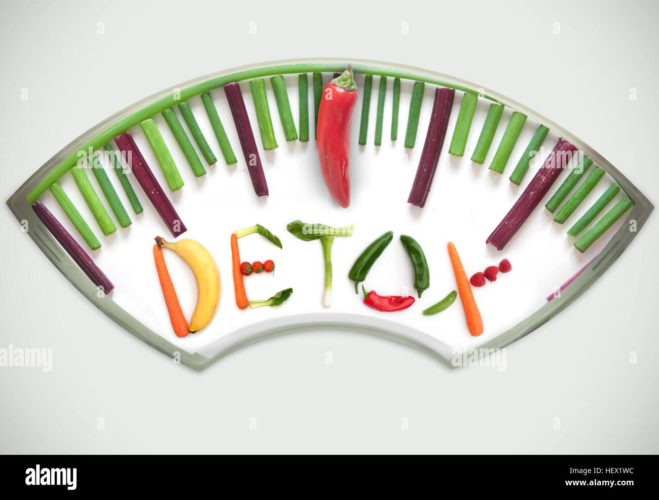 Bathroom weighing scales made of vegetables including chives, betroot and pepper, pointing towards detox - Stock Image