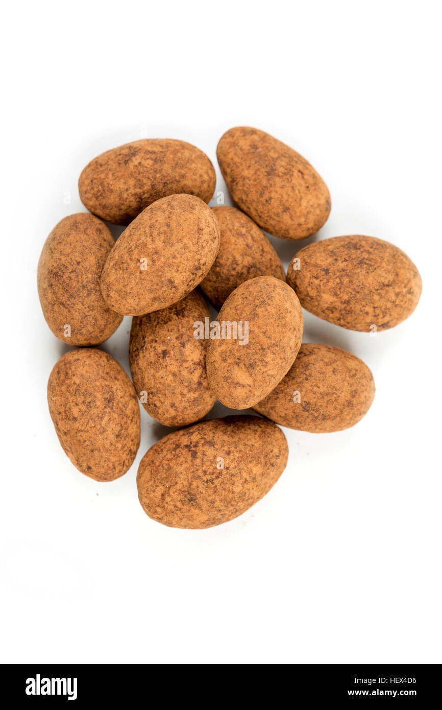 Cocoa dusted almonds isolated on white background - Stock Image