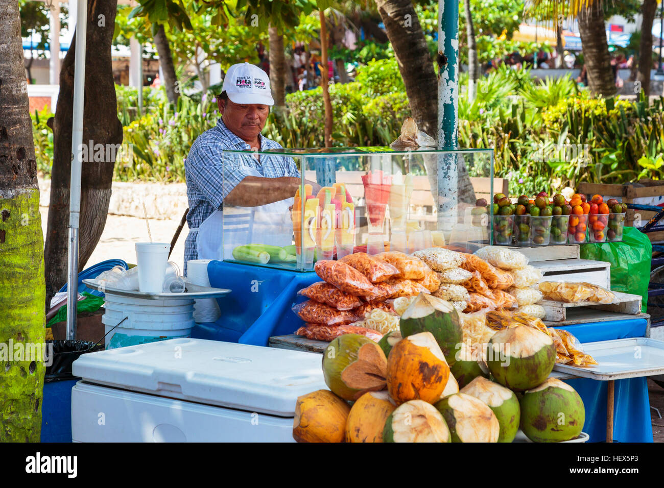 Man selling fresh fruit and corn snacks from a stall on 5th Avenue, Playa Del Carmen, Riviera Maya, Mexico - Stock Image