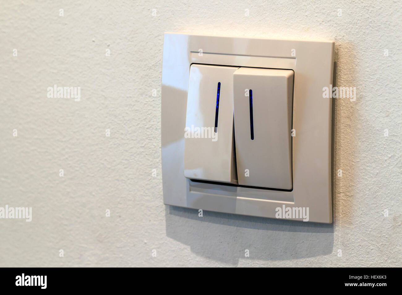 Modern white double light switch on the wall, turn on or turn off ...