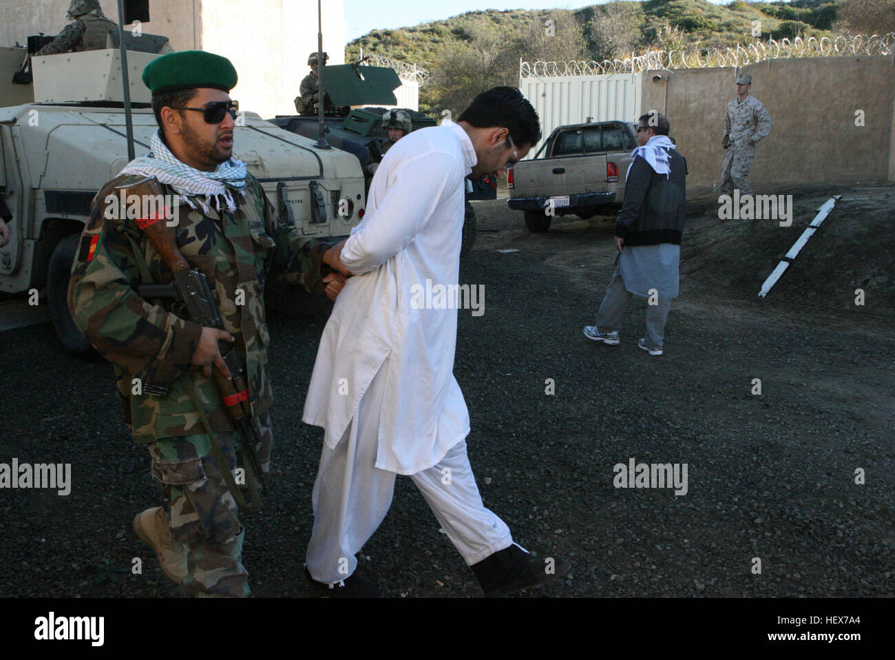 An Afghan National Policeman takes a suspected insurgent role player into custody after a simulated vehicle borne - Stock Image