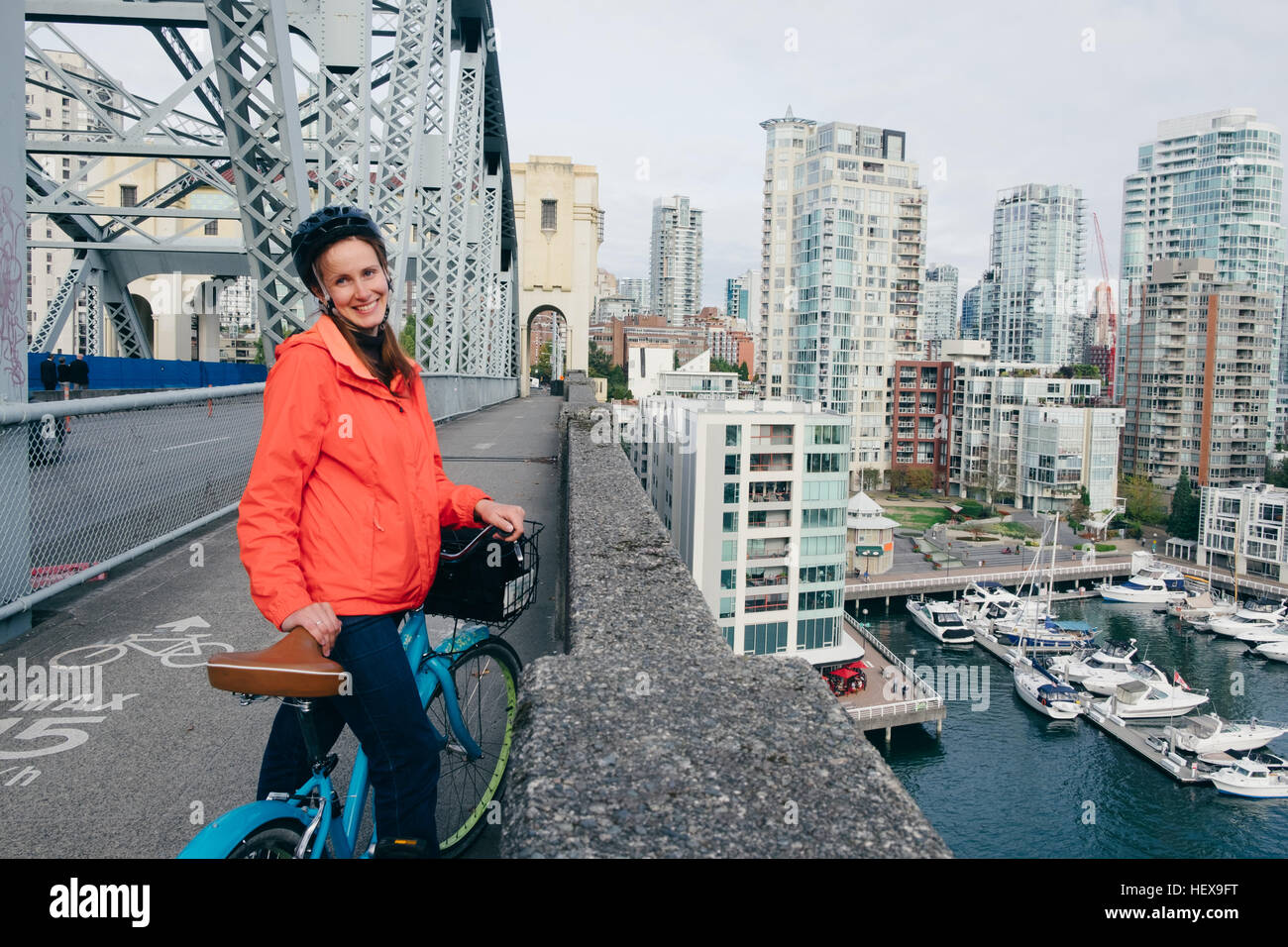 Portrait of young woman ready to ride bicycle on cycle path, Vancouver, British Columbia, Canada - Stock Image