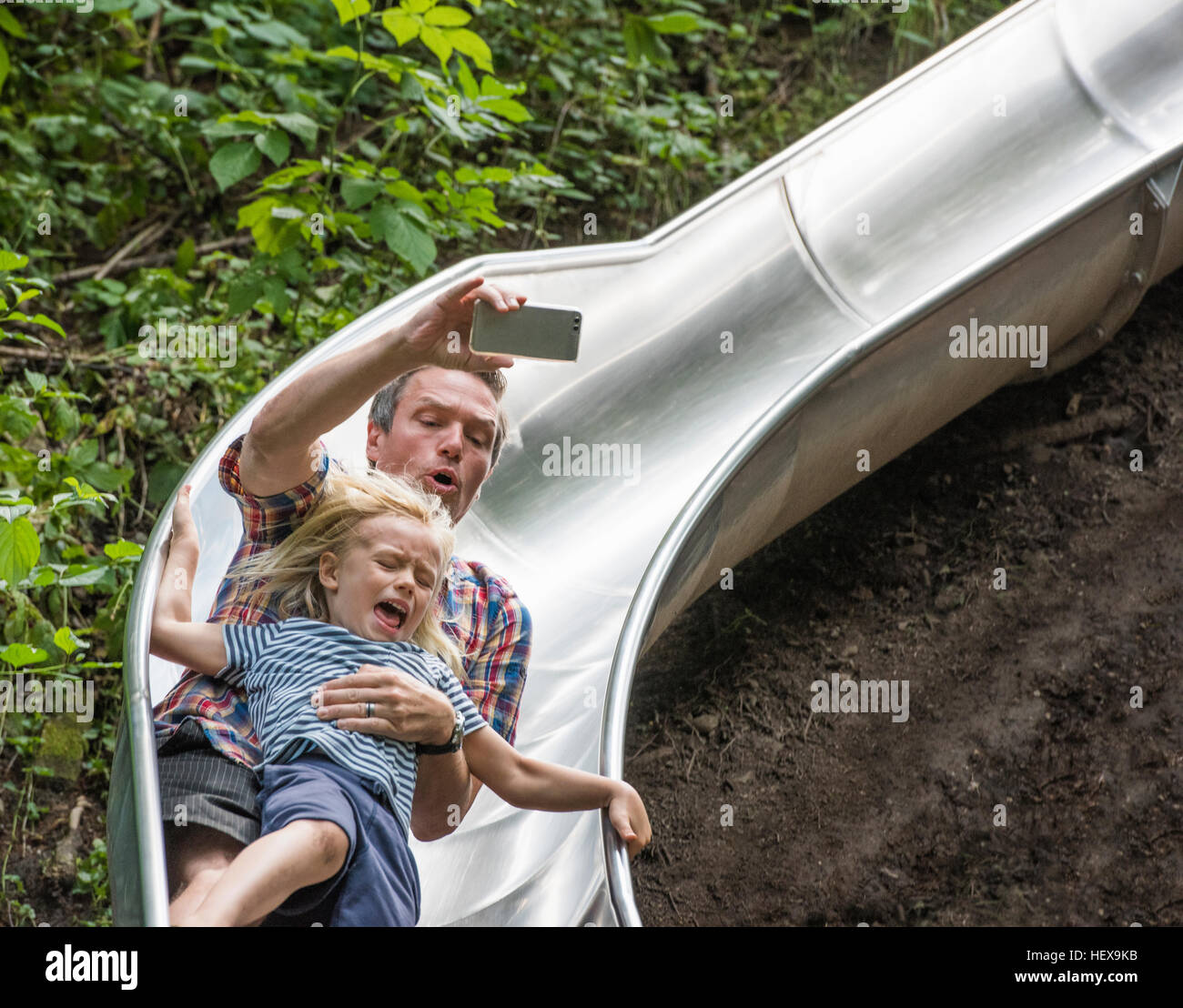 Father and son sliding down slide holding smartphone - Stock Image