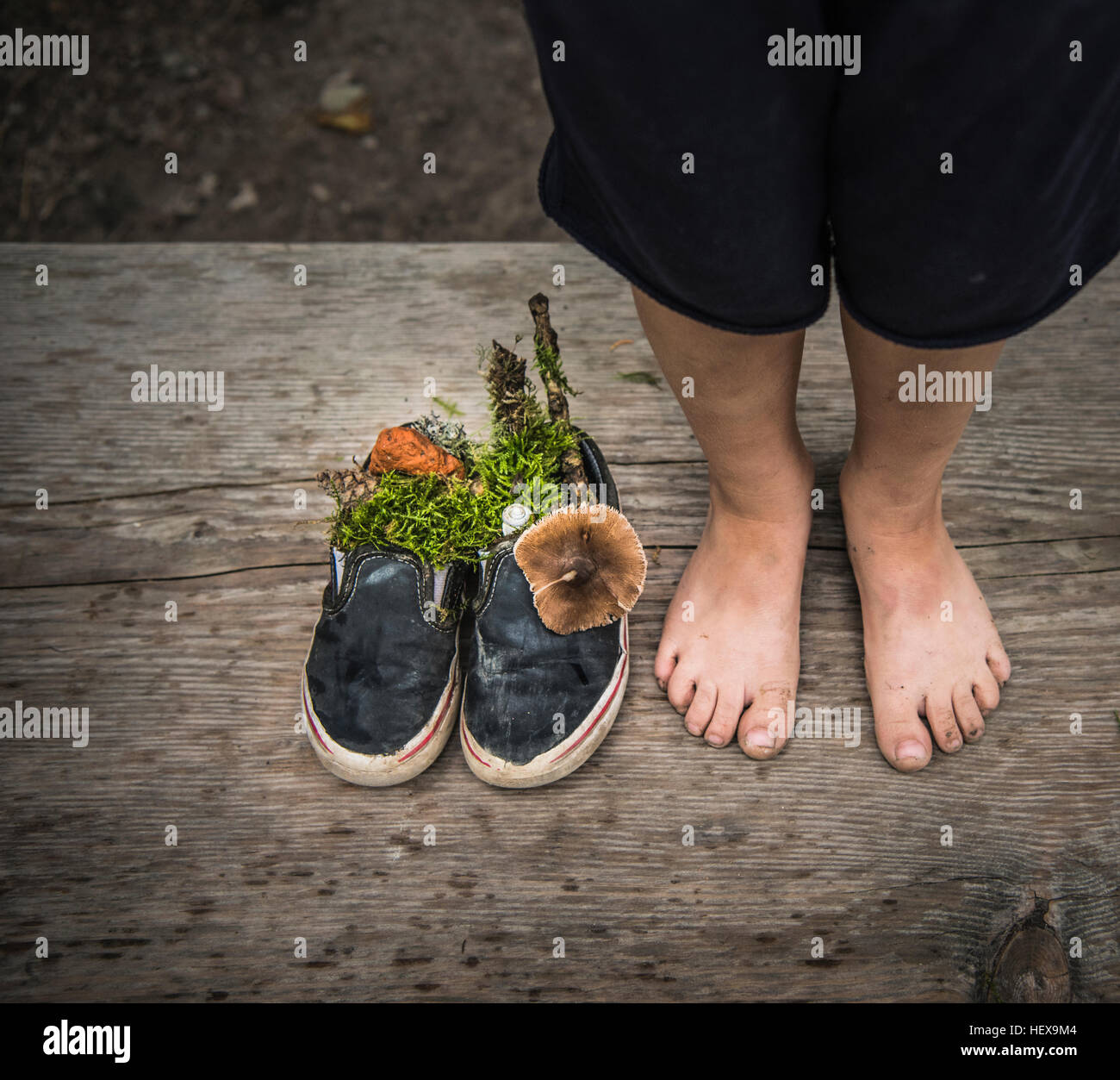 Bare feet of boy next to shoes filled with nature - Stock Image