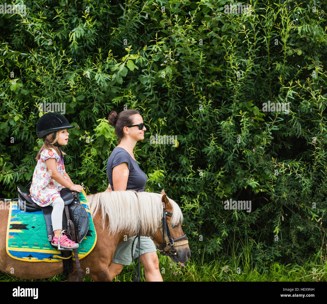 Side view of mother guiding daughter riding horse - Stock Image