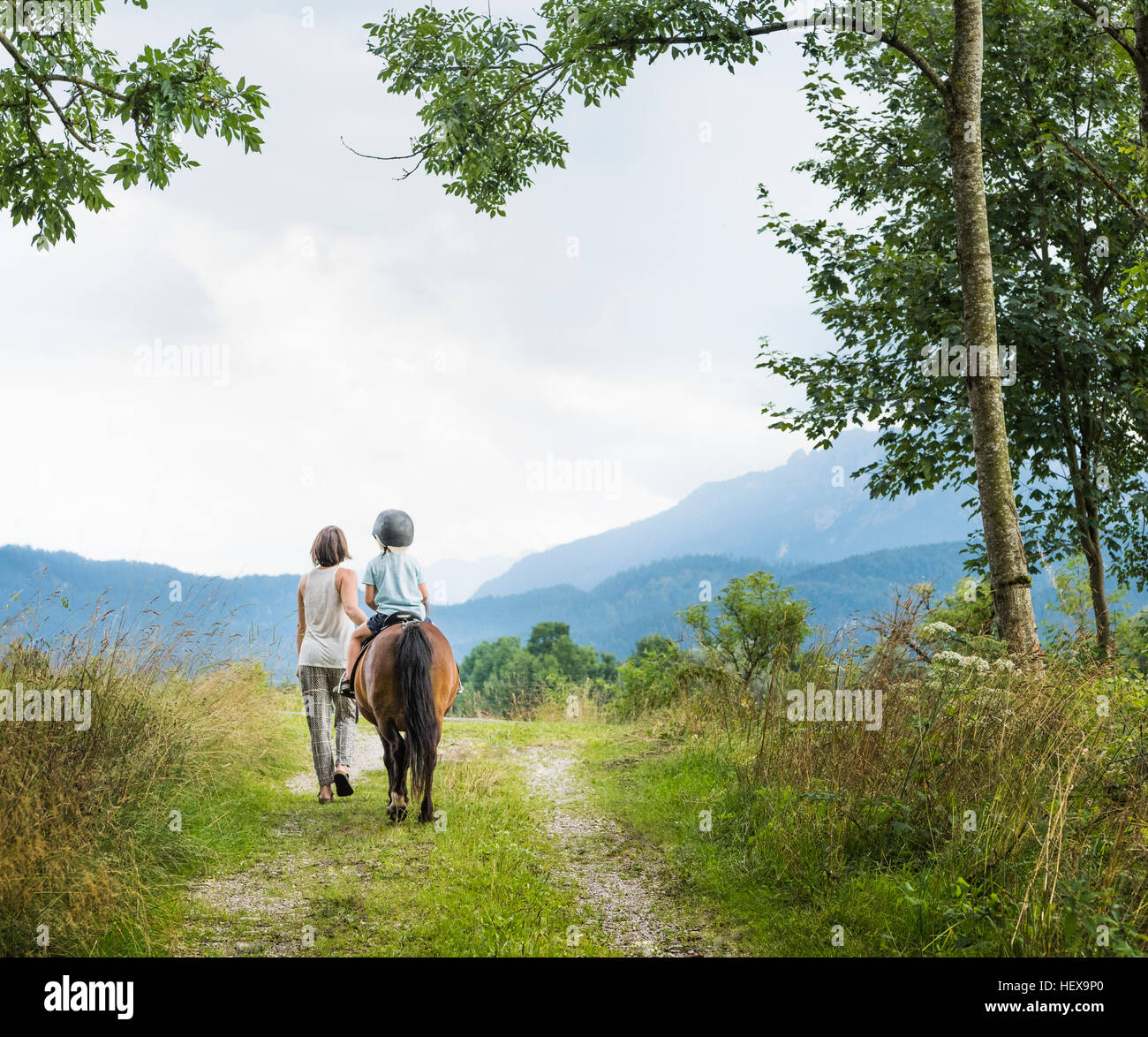 Rear view of mother guiding son riding horse, Fuessen, Bavaria, Germany - Stock Image