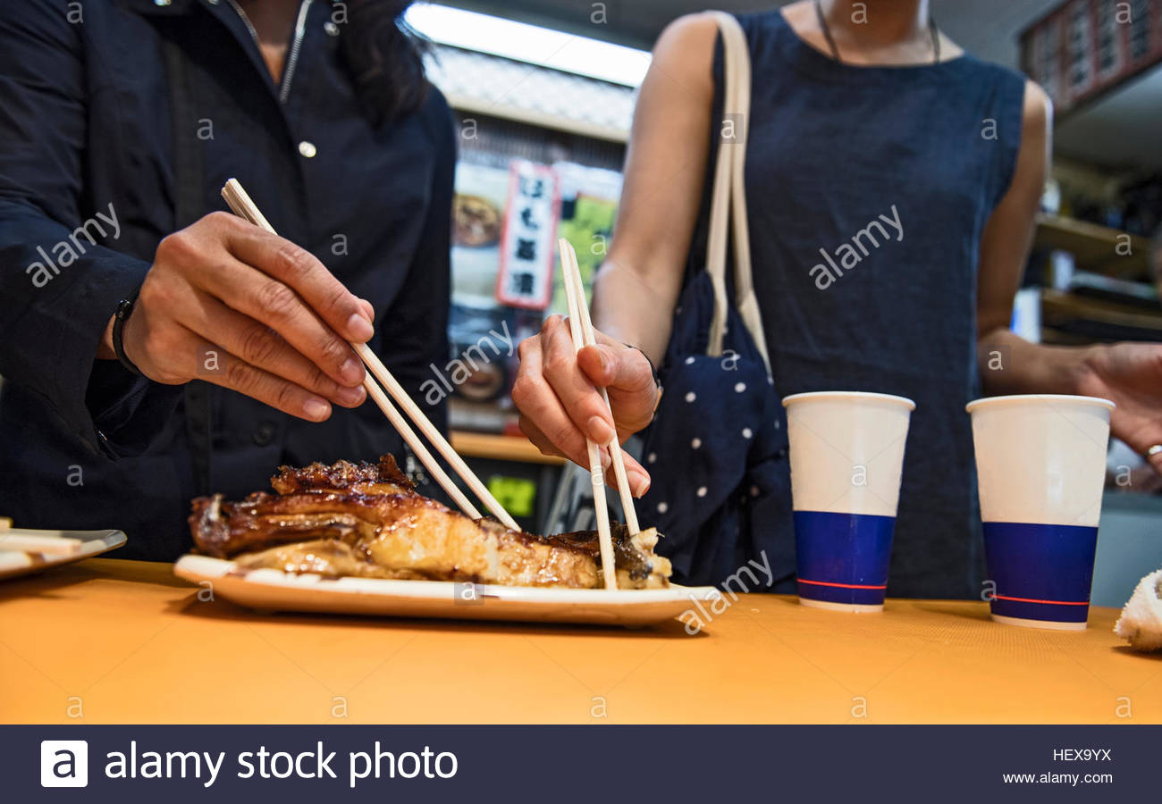 Two friends eating fish at the Nishiki street market in Kyoto, Japan - Stock Image