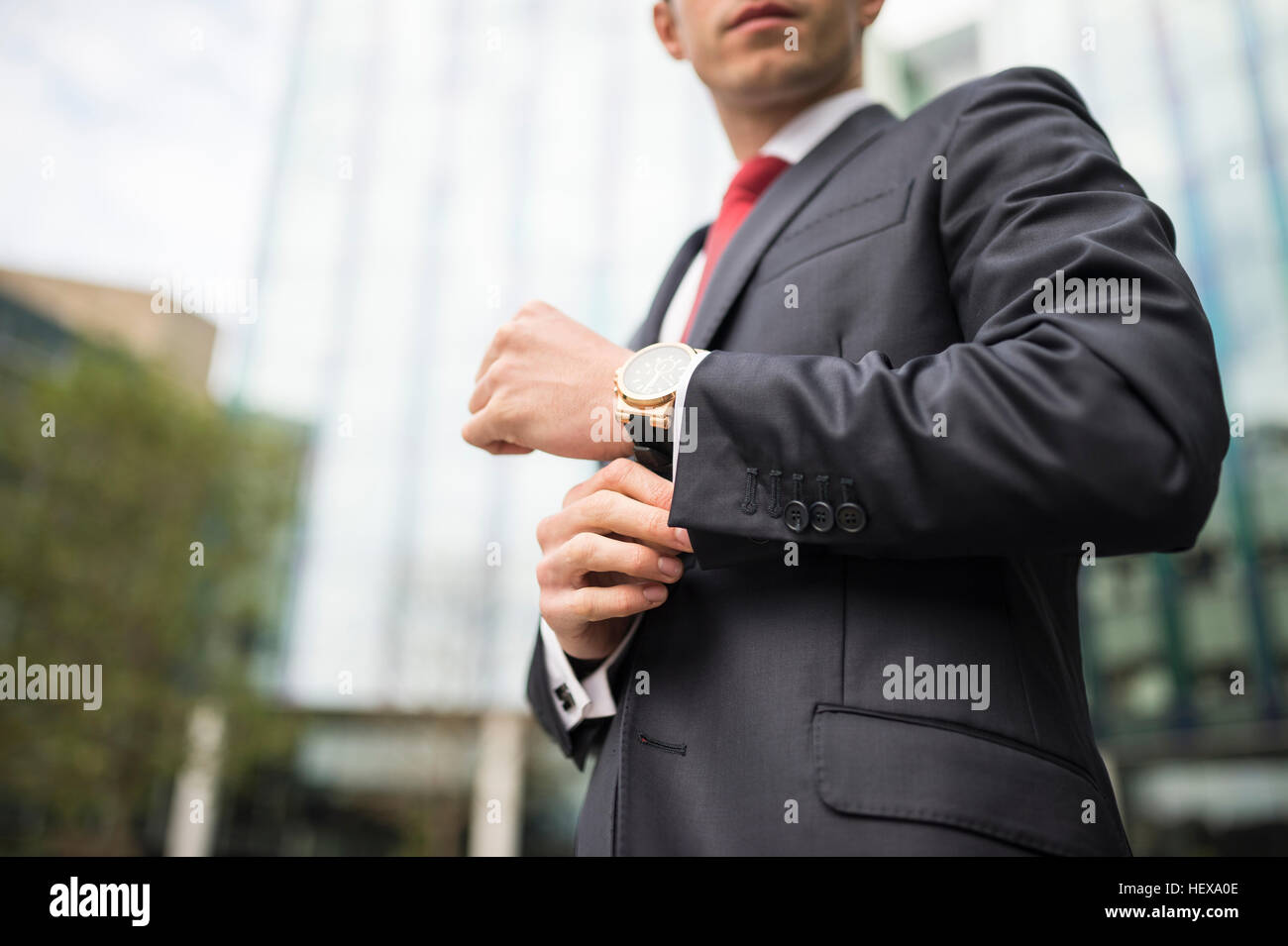 Cropped view of business man straightening cuff - Stock Image