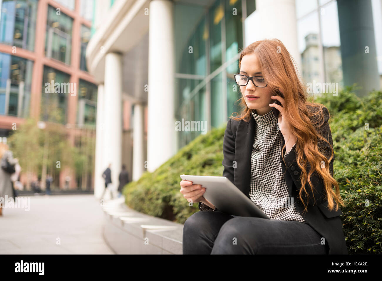 Businesswoman in city making telephone call, using digital tablet - Stock Image