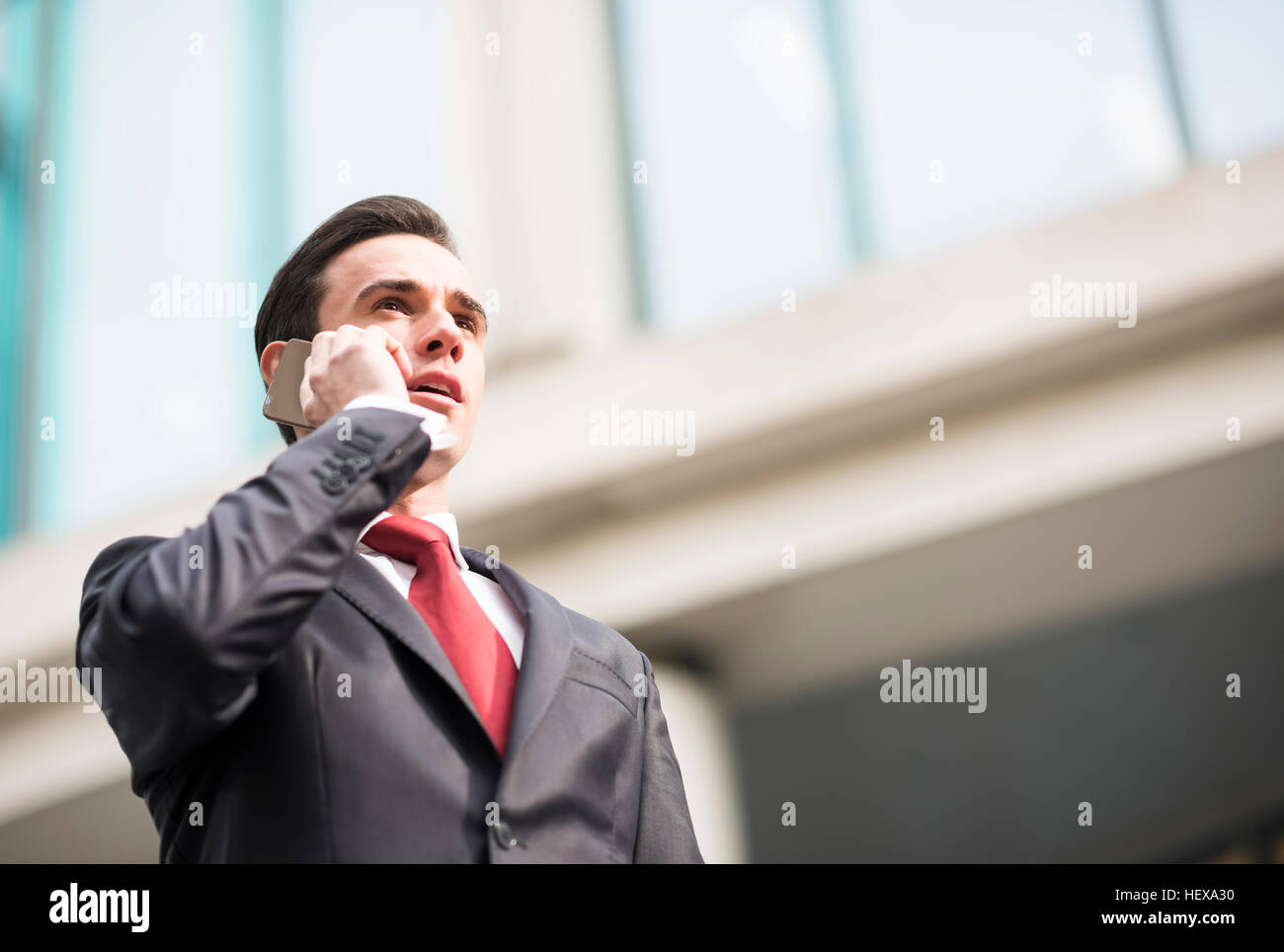 Businessman in city making telephone call - Stock Image