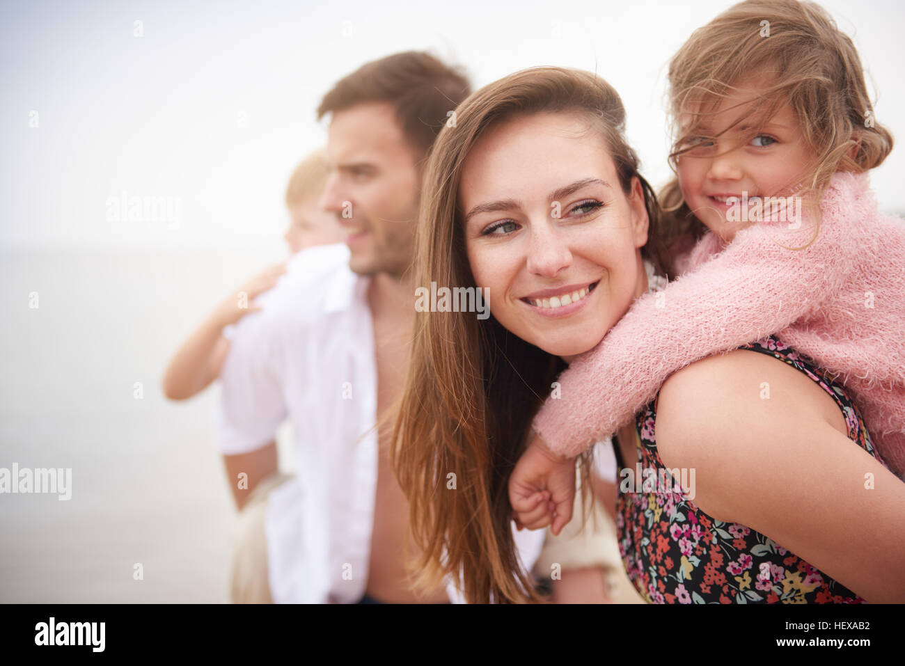 Parents giving children piggybacks on beach - Stock Image