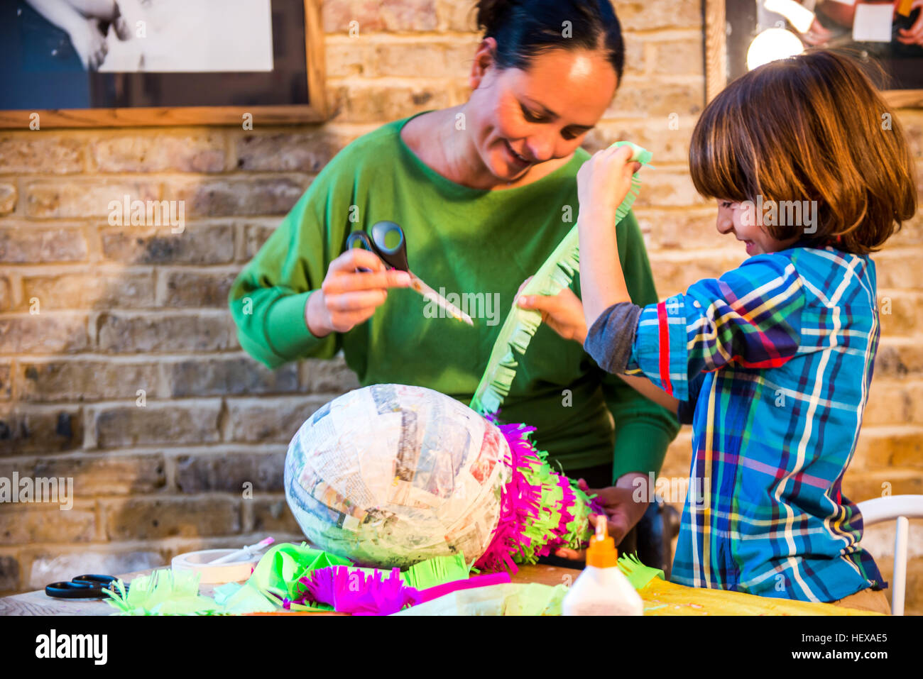 Mother and son decorating pinata at home - Stock Image