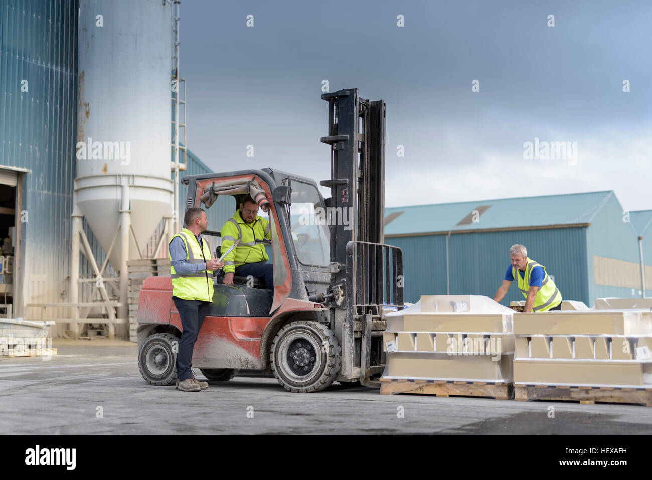 Manager talking to forklift truck driver outside architectural stone factory - Stock Image