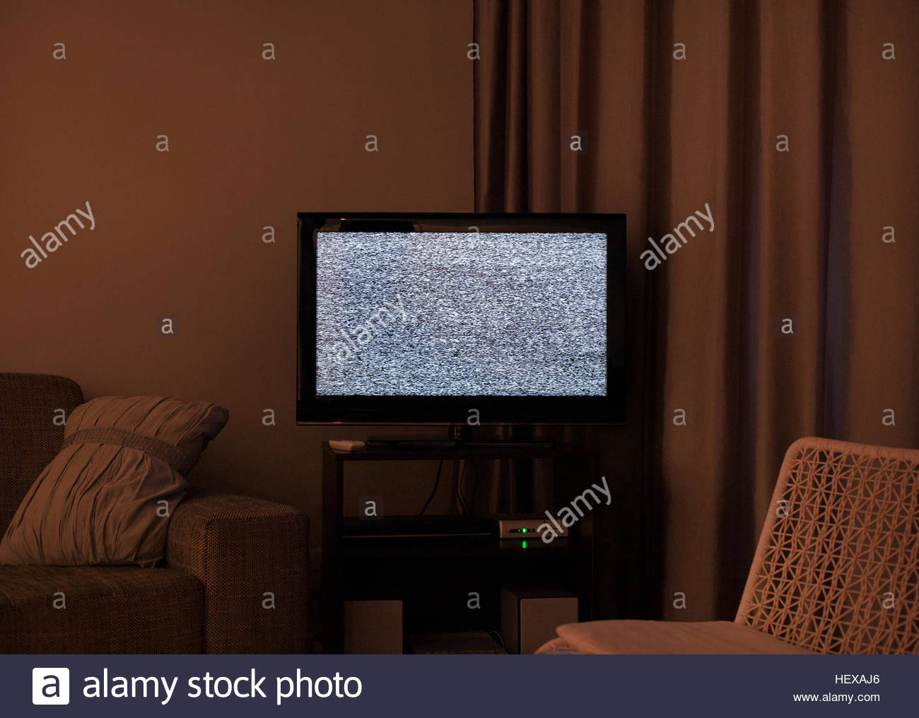 Darkened living room with static noise on TV screen - Stock Image