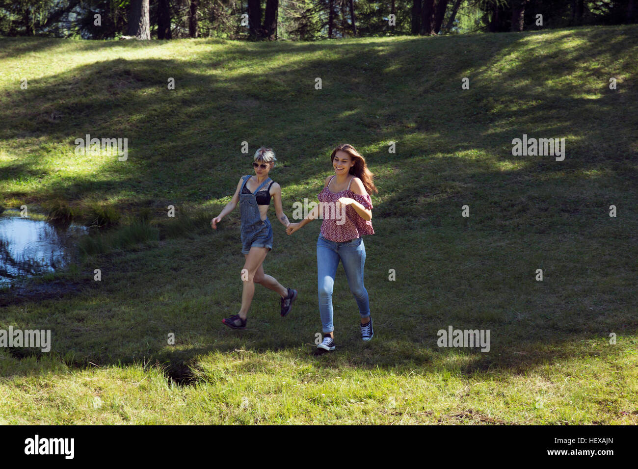 Two female friends running in forest glade, Sattelbergalm, Tyrol, Austria - Stock Image
