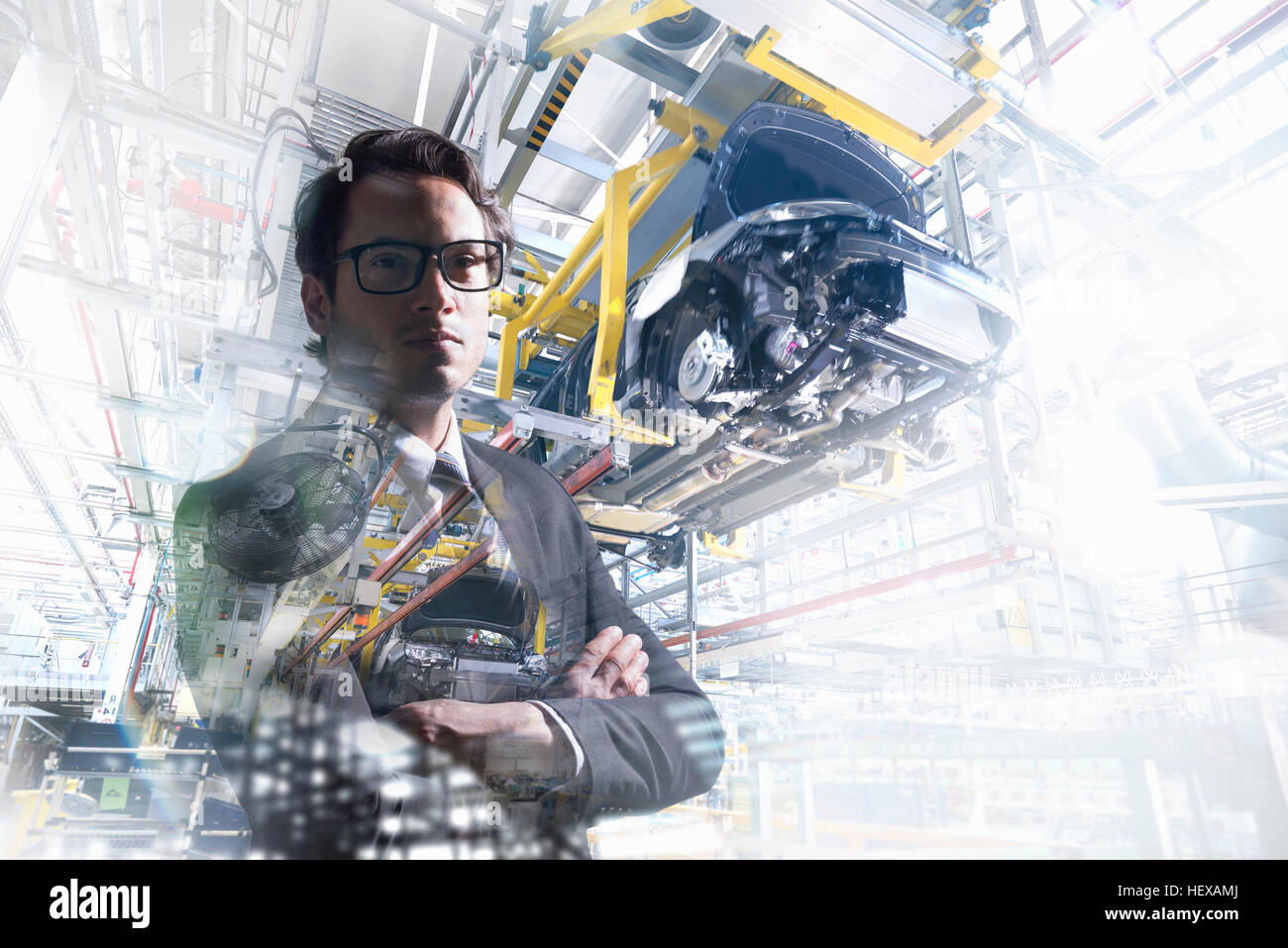 Conceptual image of businessman in car factory - Stock Image