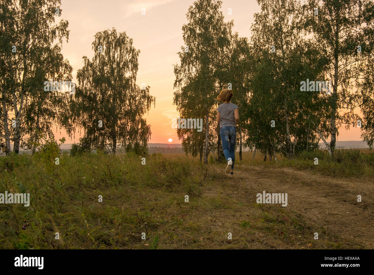 Rear view of woman running along rural dirt track at sunset Stock Photo