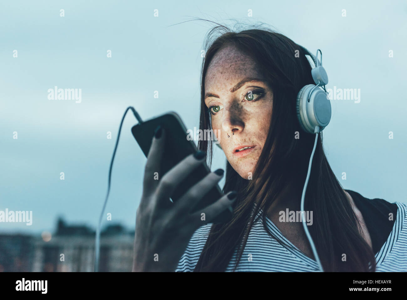 Young freckled woman listening to headphones looking at smartphone at dusk - Stock Image