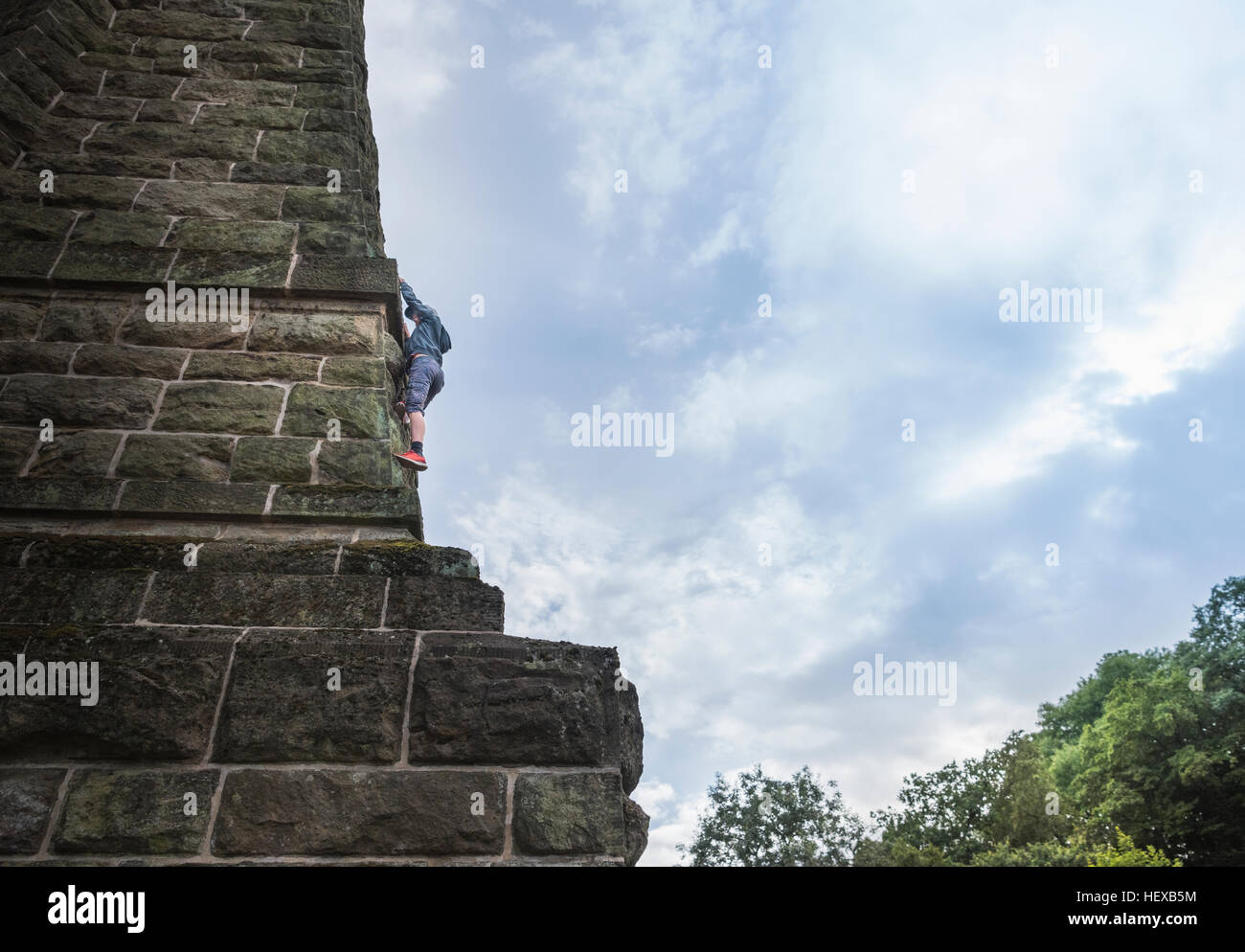 Low angle view of boy climbing stone wall - Stock Image