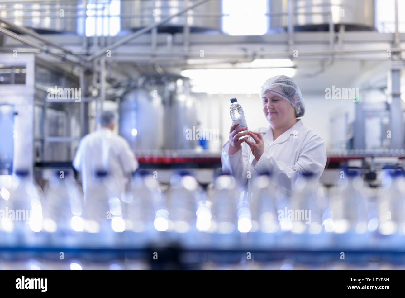 Female worker inspecting water bottle on production line in spring water factory - Stock Image