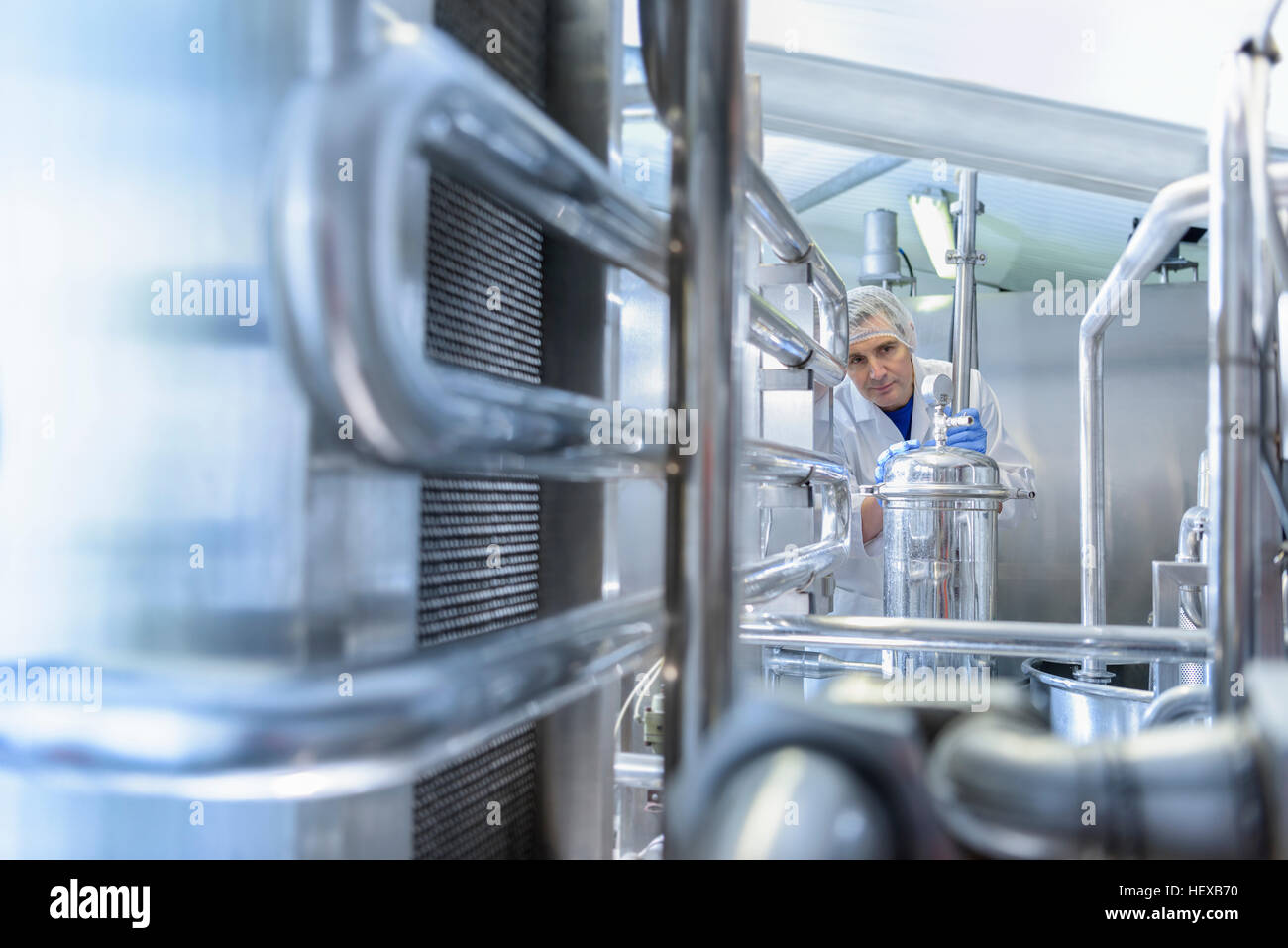 Worker with pasteurising machine in spring water factory - Stock Image