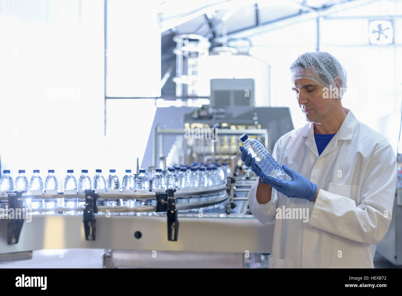 Worker inspecting water bottle on production line in spring water factory - Stock Image