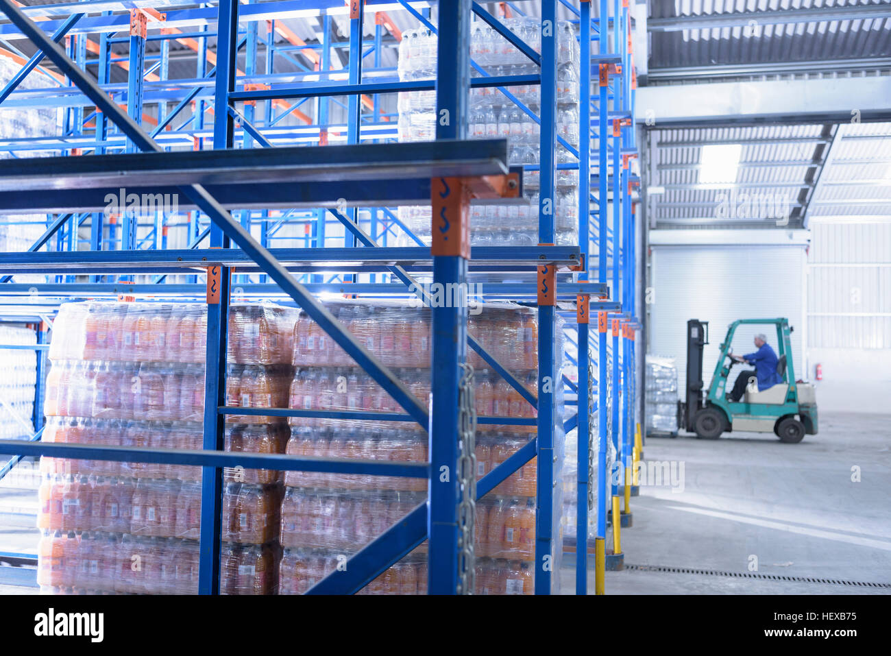 Worker packing water bottles in storage racking in spring water factory - Stock Image