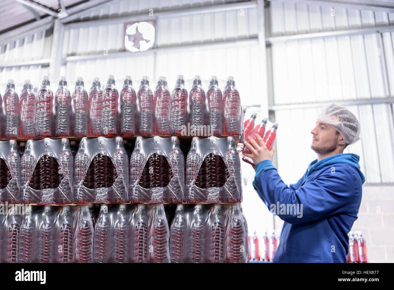 Worker packing flavoured water bottles in spring water factory - Stock Image
