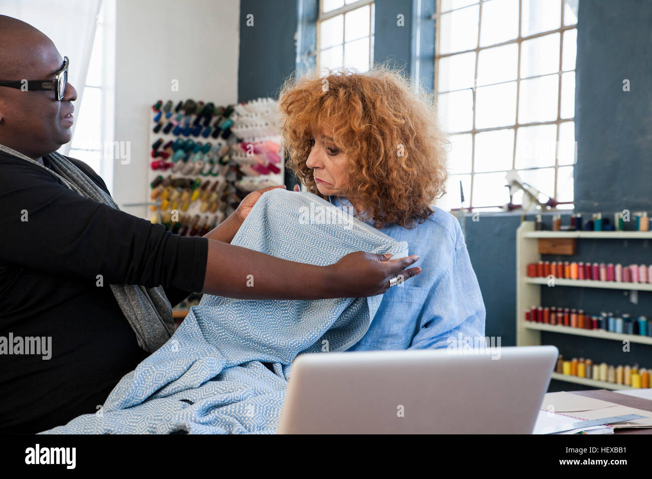 Male fashion designer trying blue material against seamstress  in design studio - Stock Image