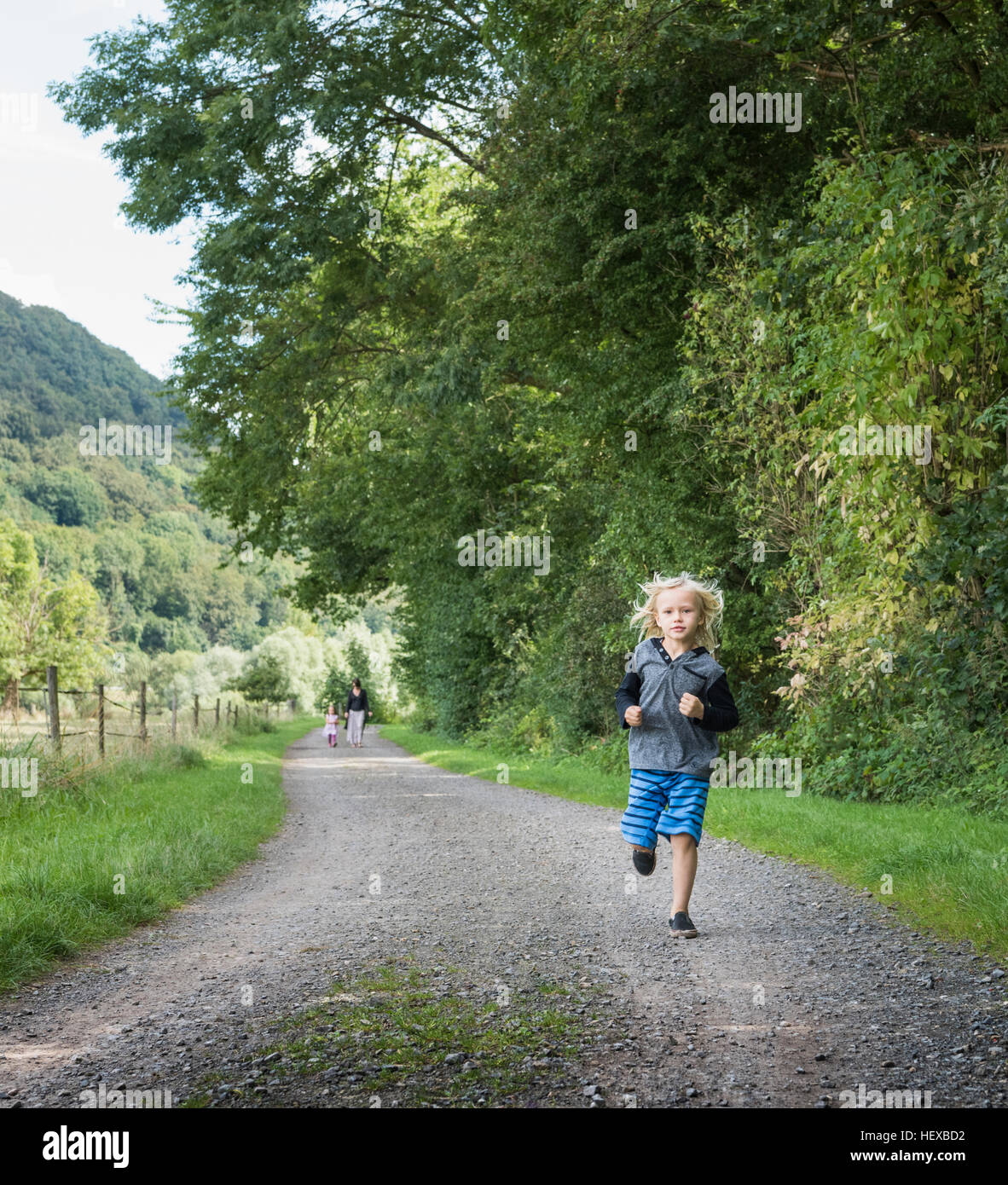 Boy with family running on rural road, Porta Westfalica, North Rhine Westphalia, Germany Stock Photo