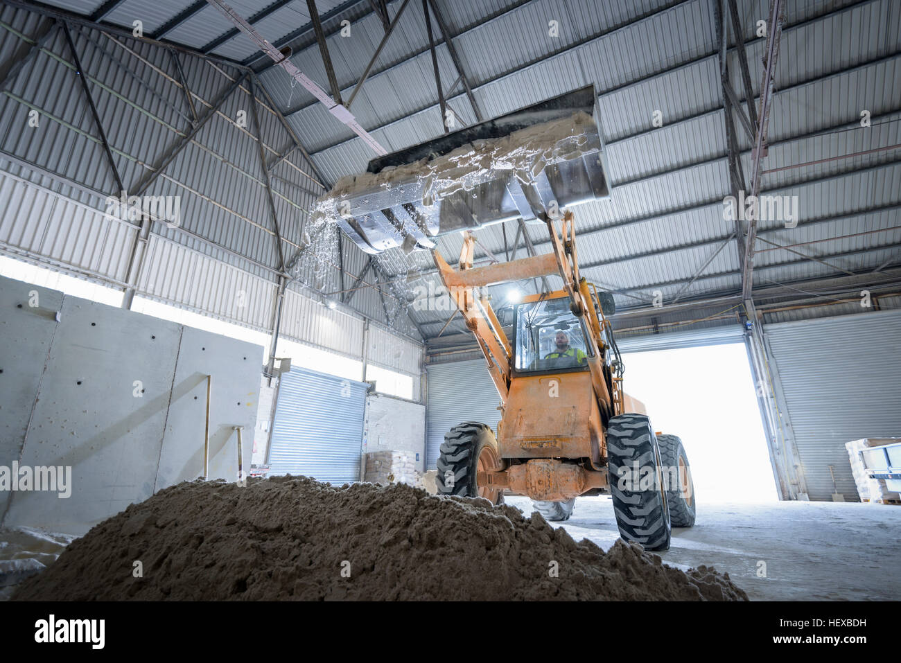 Digger with sand in architectural stone factory - Stock Image