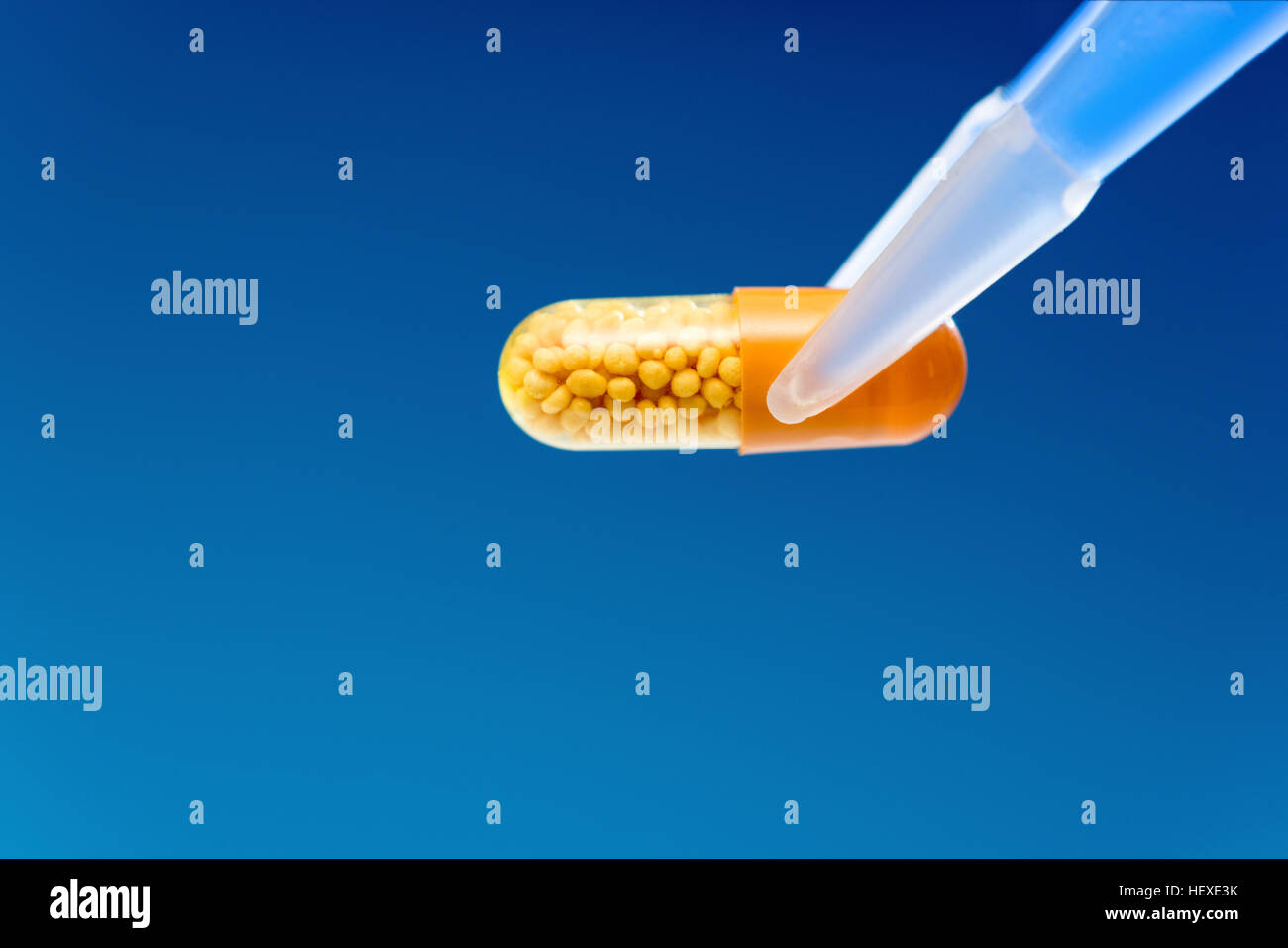 Capsule against a blue background. - Stock Image