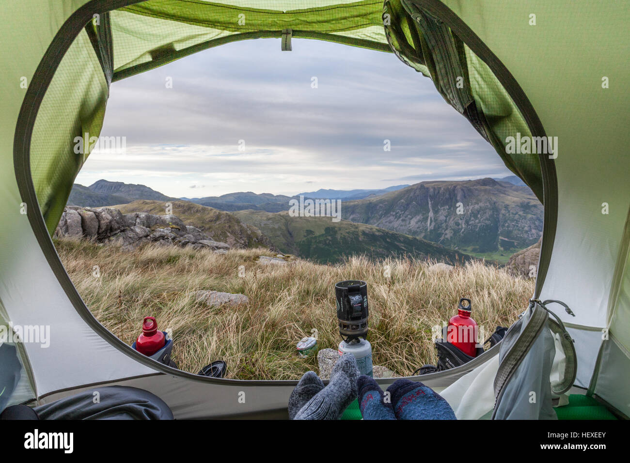 Room with a view - Wild camping couple pair of feet, looking out of tent porch to Langdale Pikes in the English - Stock Image
