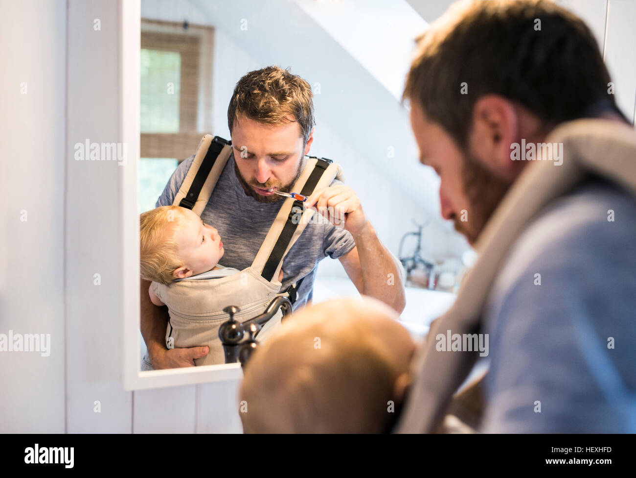 Father with baby in baby carrier brushing his teeth - Stock Image