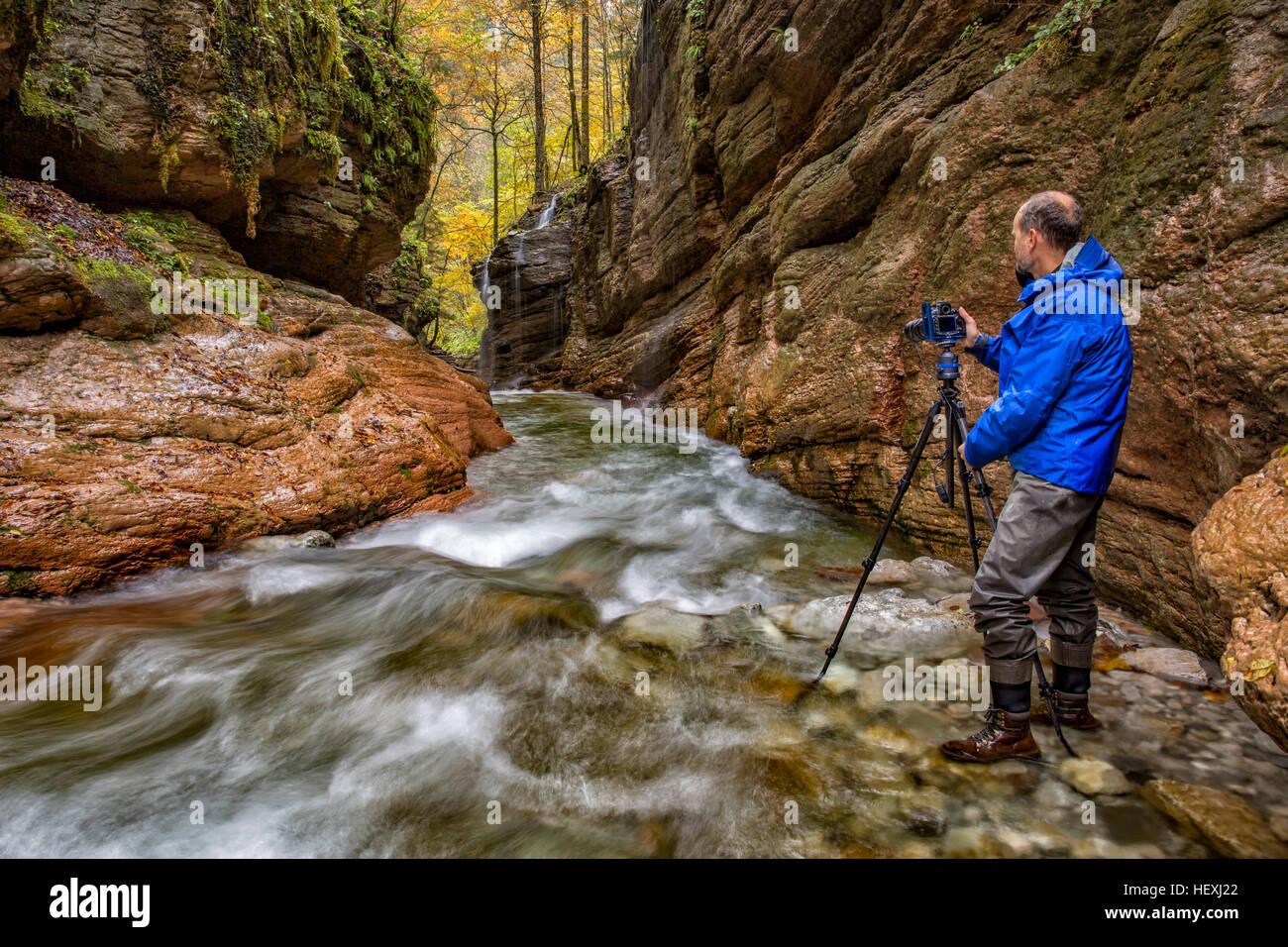Austria, Tennegau, Photographer standing at Taugl river Stock Photo