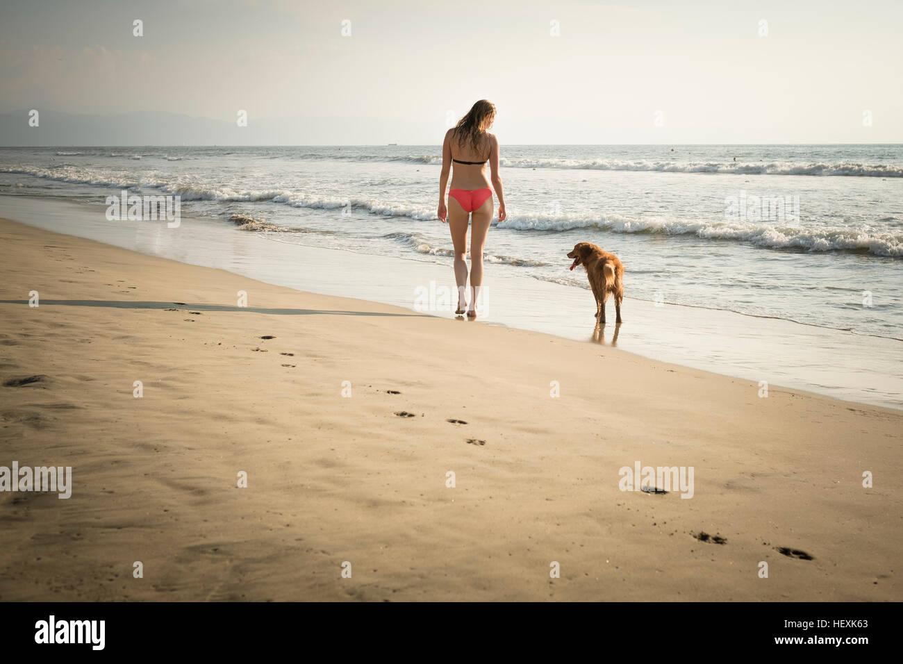 Mexico, Riviera Nayarit, Woman walking with dog at the beach - Stock Image