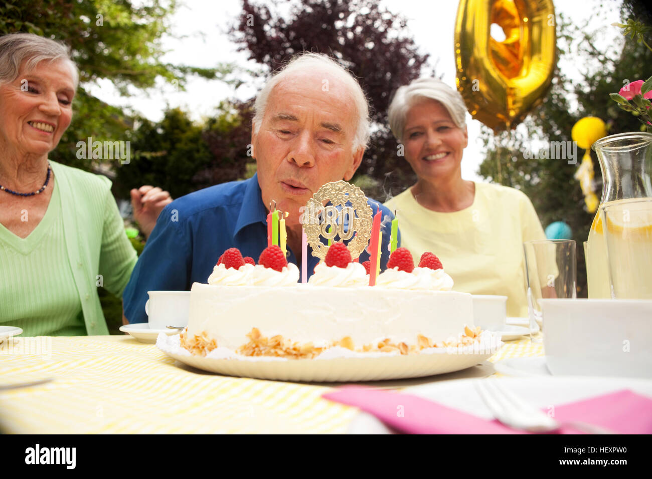 Senior Man Blowing Candle On 80th Birthday Cake