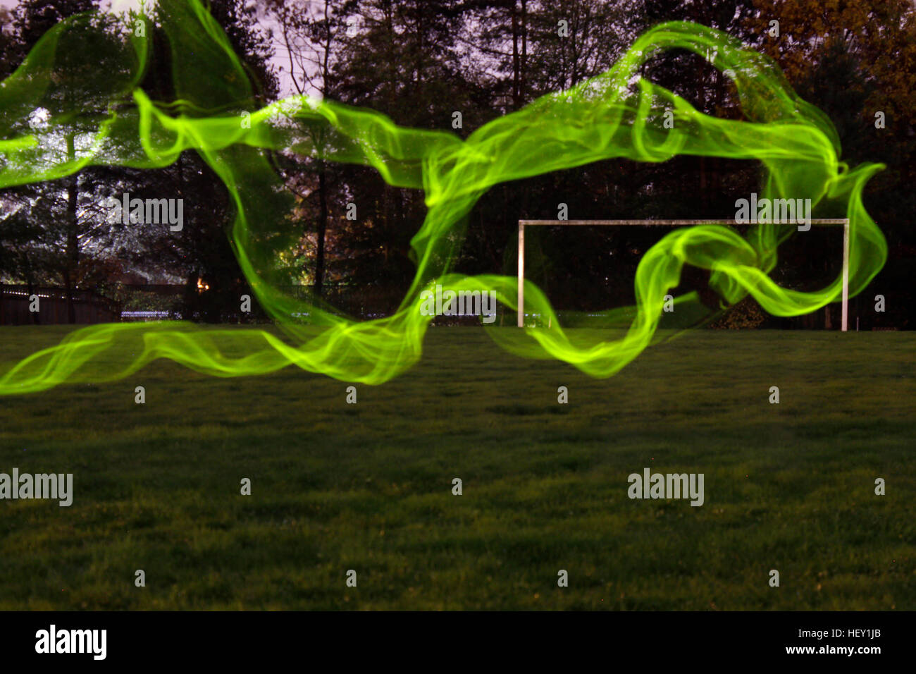 Green ectoplasm moving through the green grass. - Stock Image