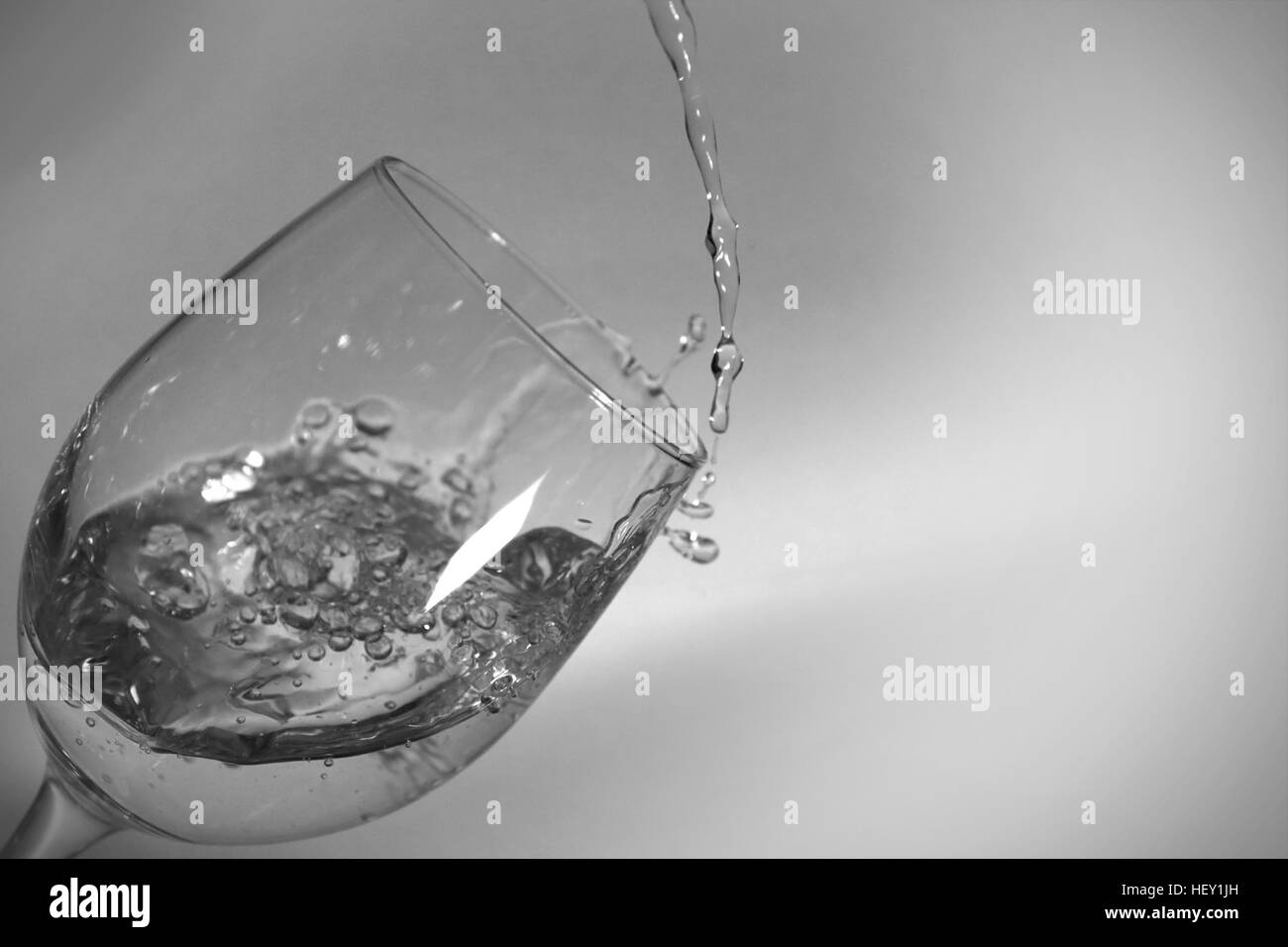 Fast shutter speed of water filling a tilted wine glass. - Stock Image