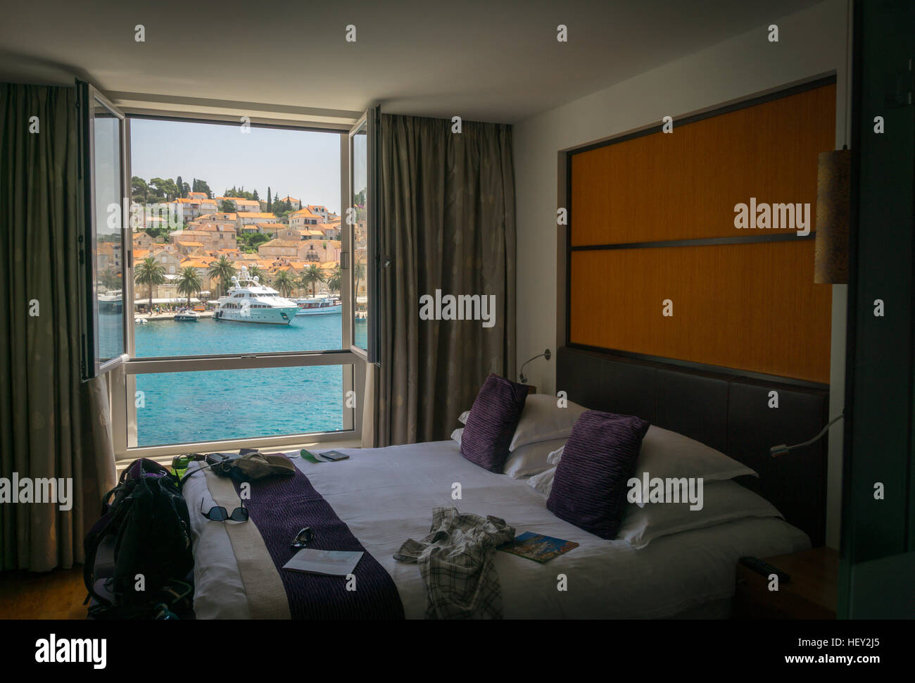 Looking out a window onto the beautiful port of Hvar Town, on the island of Hvar in Croatia, with a bed with suitcase, - Stock Image
