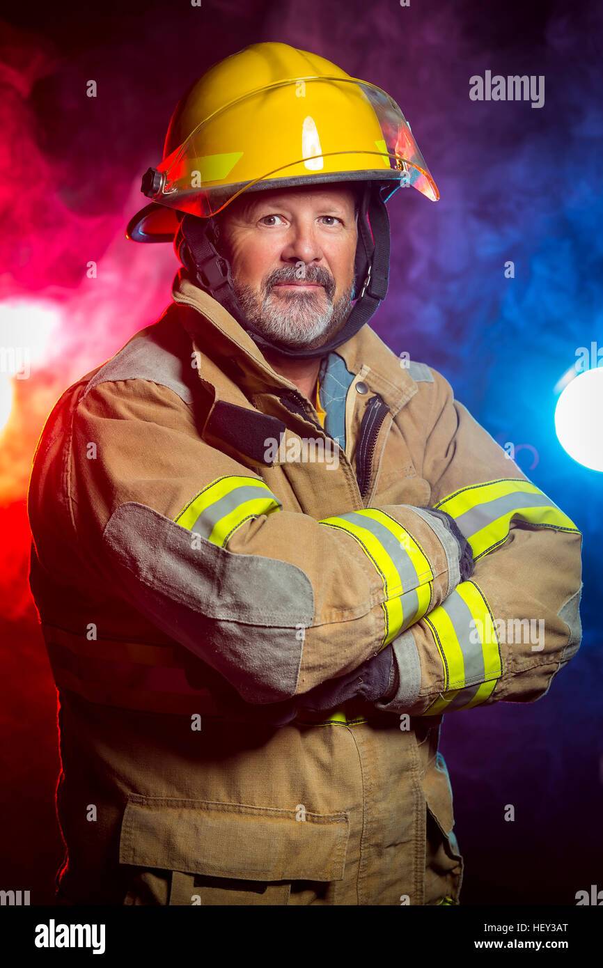 Portrait of a fireman wearing Fire Fighter turnouts and helmet. Background is red and blue smoke and light. Turnouts - Stock Image