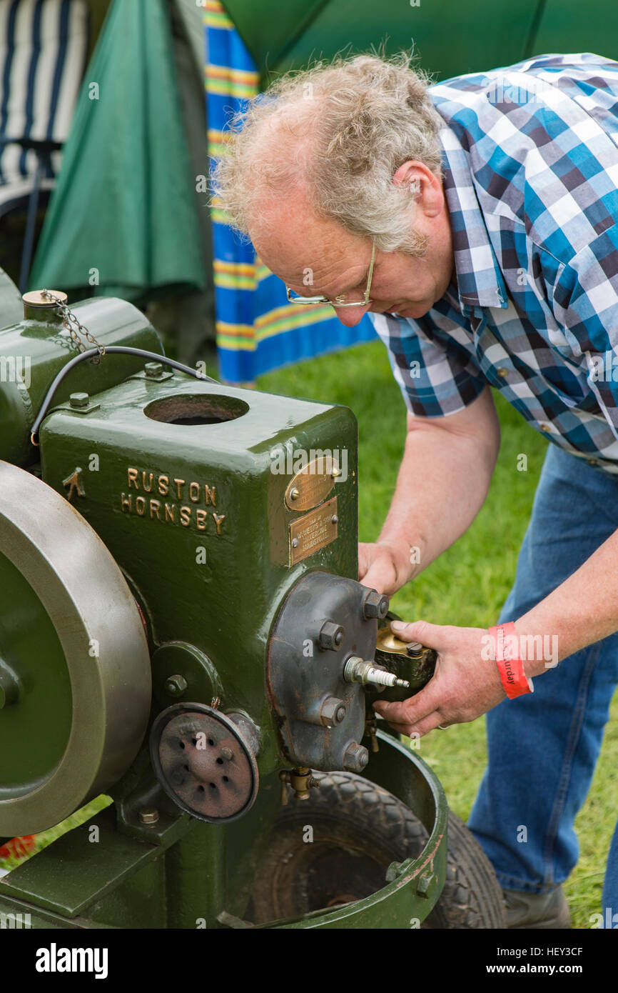 A man adjusts a Stationary Engine at a county show. Stock Photo