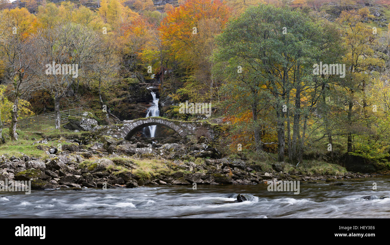 A waterfall flows under an old stone packhorse bridge along Glen Lyon Stock Photo