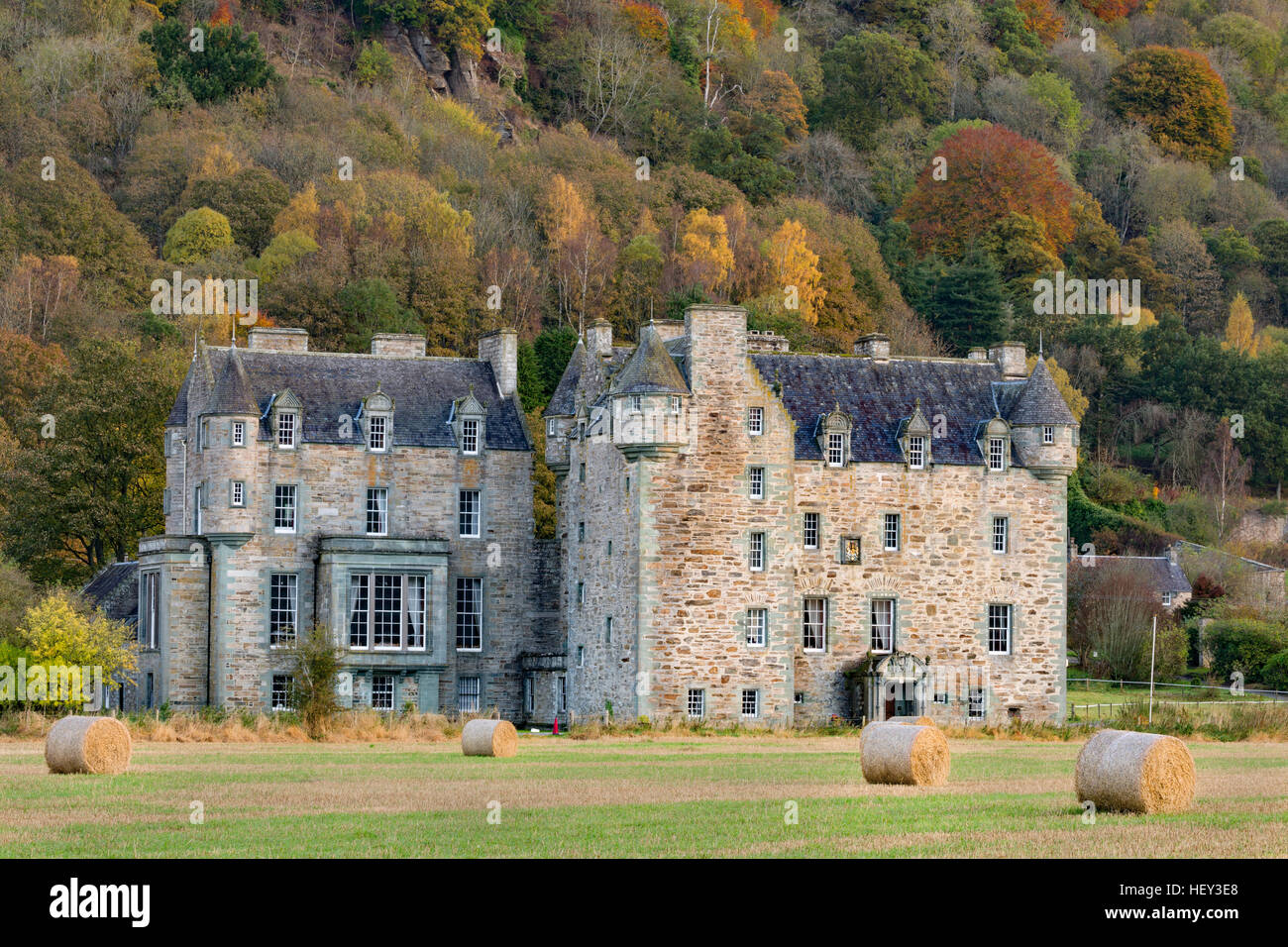 Castle Menzies, Weem, Pertshire, with hay bales in the fireground and a woodland in Autumn colours in the background. - Stock Image